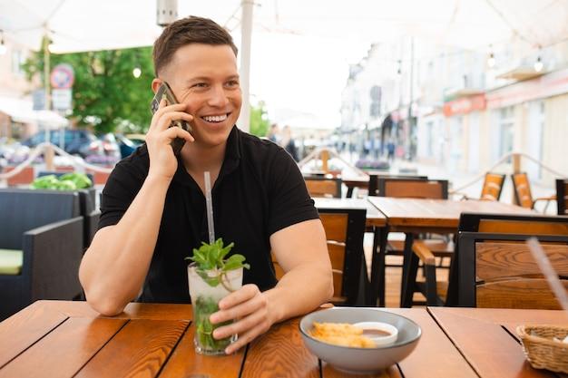 Homem jovem empresário sentado à mesa de um café de rua e fala sobre fundo inteligente