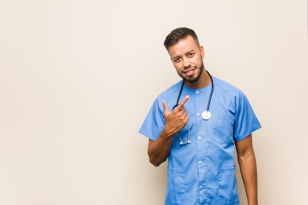 Homem jovem enfermeira sul-asiática apontando com o dedo para você como se fosse um convite para se aproximar.
