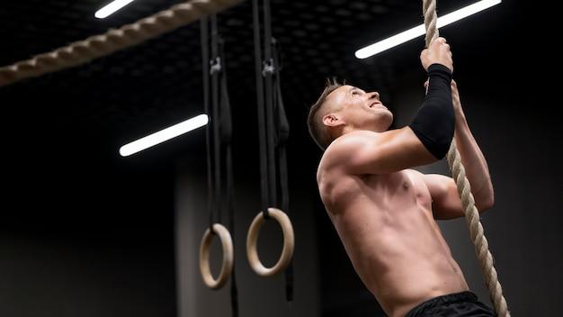 Homem jovem, escalando corda