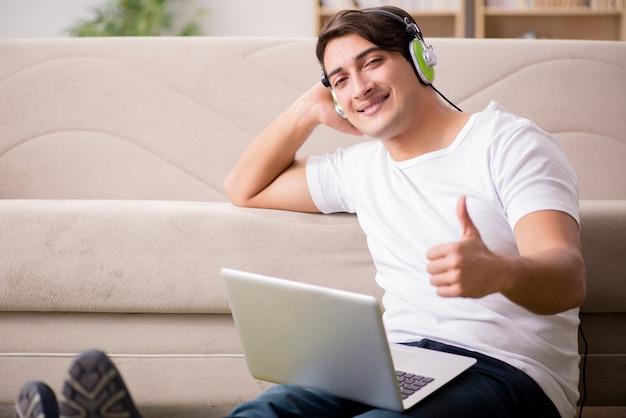Homem jovem, escutar música, de, laptop