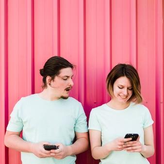 Homem jovem, espiando, e, espiando, em, smartphone, de, dela, namorada, usando, telefone móvel