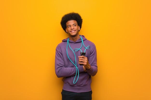 Homem jovem esporte americano africano segurando uma corda de pular sorrindo confiante e cruzando os braços, olhando para cima