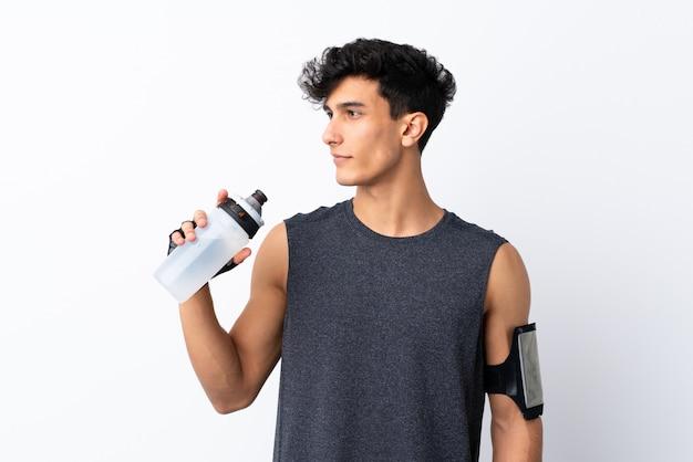 Homem jovem esporte argentino isolado parede branca com garrafa de água de esportes
