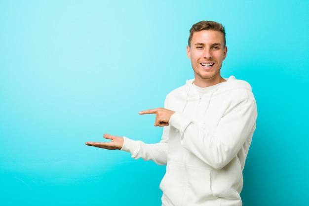 Homem jovem esporte caucasiano animado segurando uma cópia na palma da mão.
