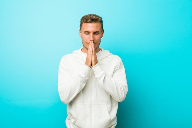 Homem jovem esporte caucasiano de mãos dadas em rezar perto da boca, sente-se confiante.