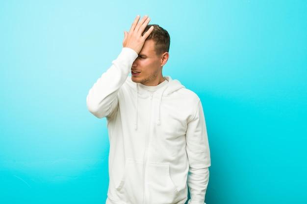Homem jovem esporte caucasiano esquecendo algo, batendo na testa com a palma da mão e fechando os olhos.