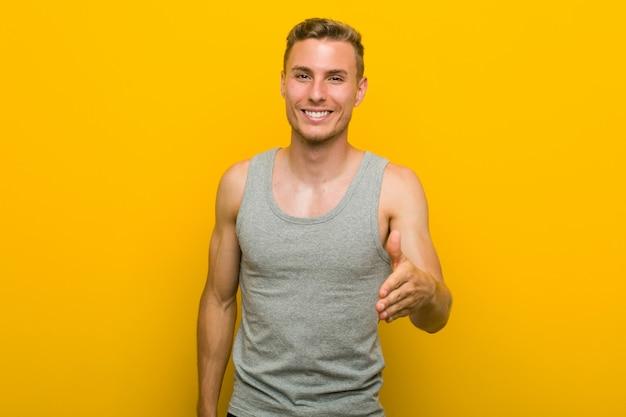 Homem jovem esporte caucasiano, esticando a mão na câmera em gesto de saudação.