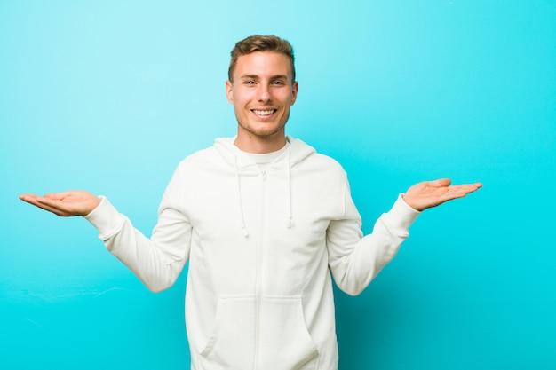 Homem jovem esporte caucasiano faz escala com os braços, sente-se feliz e confiante.