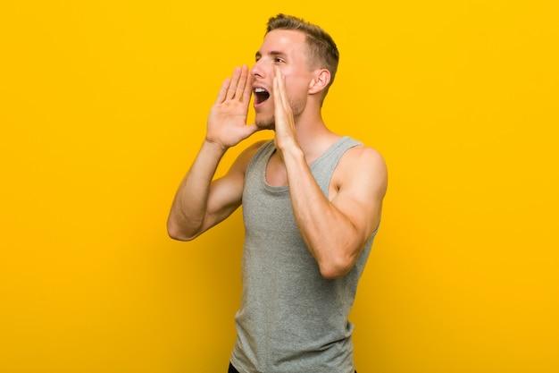 Homem jovem esporte caucasiano grita alto, mantém os olhos abertos e mãos tensas.