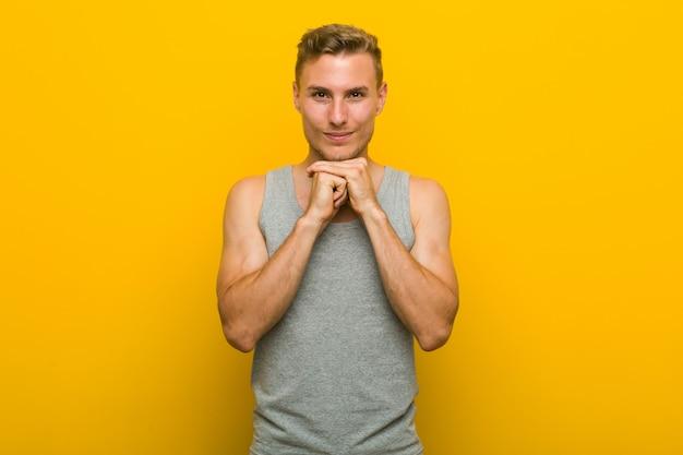 Homem jovem esporte caucasiano mantém as mãos sob o queixo, está olhando alegremente de lado.