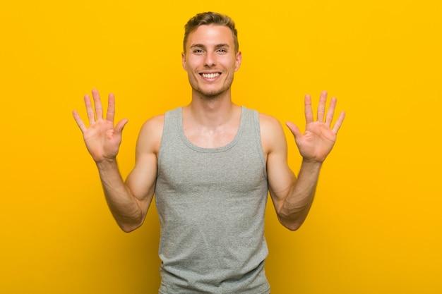 Homem jovem esporte caucasiano mostrando o número dez com as mãos.