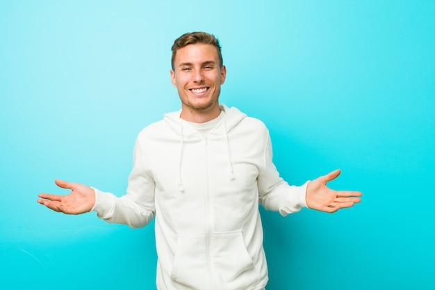Homem jovem esporte caucasiano mostrando uma expressão de boas-vindas.