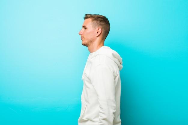 Homem jovem esporte caucasiano, olhando para a esquerda, pose de lado.