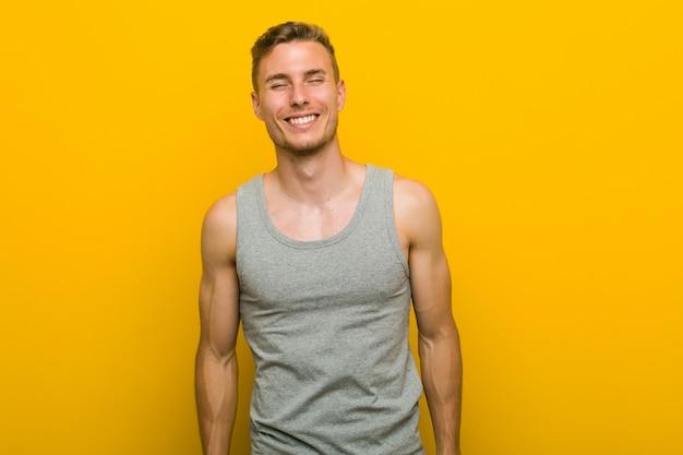 Homem jovem esporte caucasiano ri e fecha os olhos, sente-se relaxado e feliz.