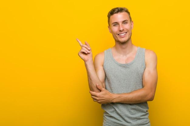 Homem jovem esporte caucasiano sorrindo alegremente apontando com o dedo indicador fora.