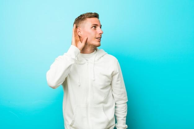 Homem jovem esporte caucasiano tentando ouvir uma fofoca.