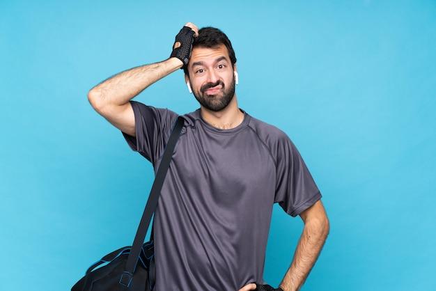 Homem jovem esporte com barba sobre parede azul isolada com uma expressão de frustração e não compreensão