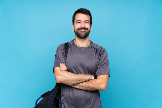 Homem jovem esporte com barba sobre parede azul isolada, mantendo os braços cruzados na posição frontal