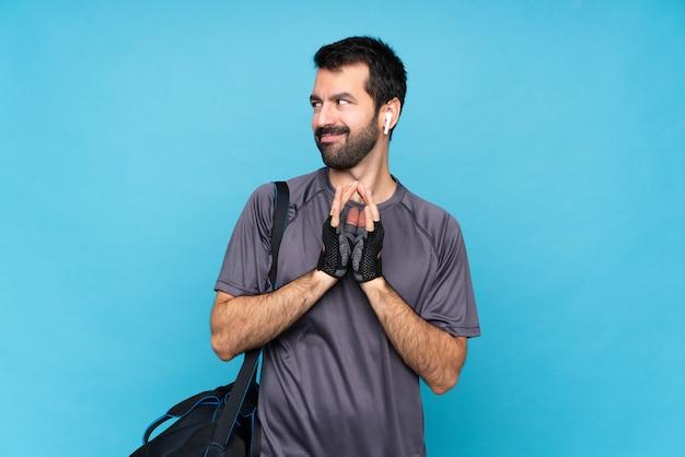 Homem jovem esporte com barba sobre parede azul isolada planejando algo