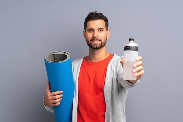 Homem jovem esporte com esteira e com uma garrafa de água
