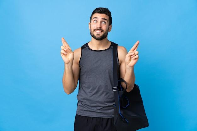 Homem jovem esporte com saco de esporte isolado na parede azul com dedos cruzando e desejando o melhor