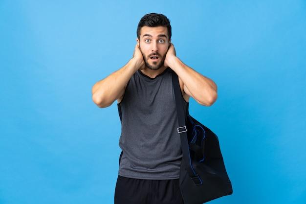 Homem jovem esporte com saco de esporte isolado na parede azul frustrado e cobrindo as orelhas