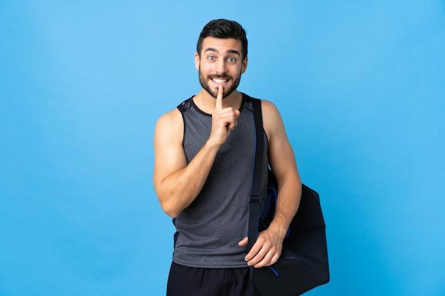 Homem jovem esporte com saco de esporte isolado na parede azul, mostrando um sinal de gesto de silêncio colocando o dedo na boca