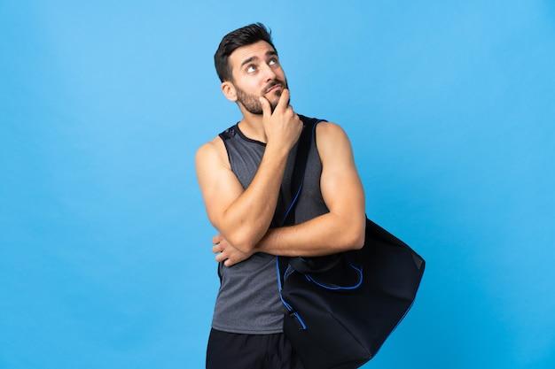 Homem jovem esporte com saco de esporte isolado na parede azul, tendo dúvidas