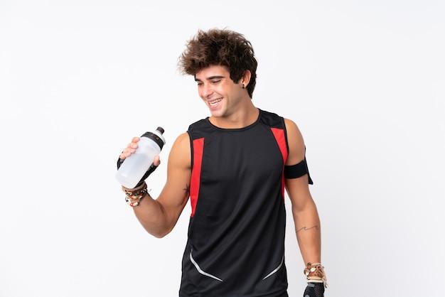 Homem jovem esporte com tatuagens sobre parede branca isolada com garrafa de água de esportes