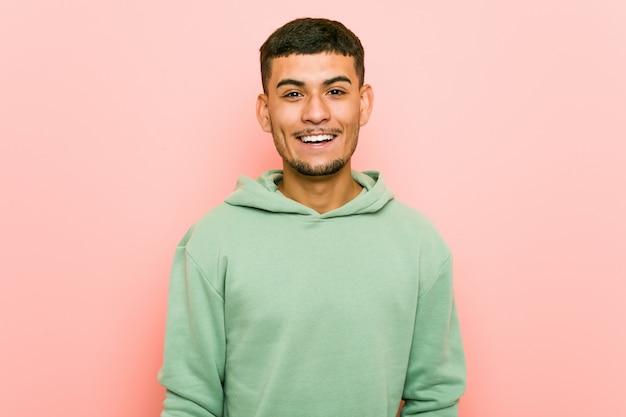Homem jovem esporte latino-americano feliz, sorridente e alegre.