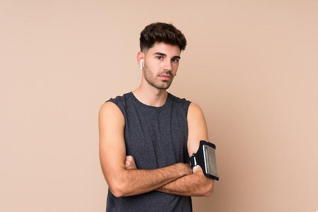 Homem jovem esporte mais isolado com os braços cruzados