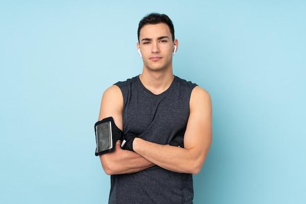 Homem jovem esporte mais isolado na parede azul com os braços cruzados