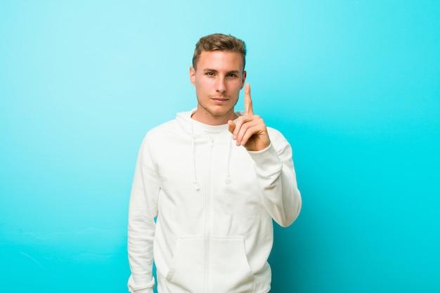 Homem jovem esporte mostrando o número um com o dedo
