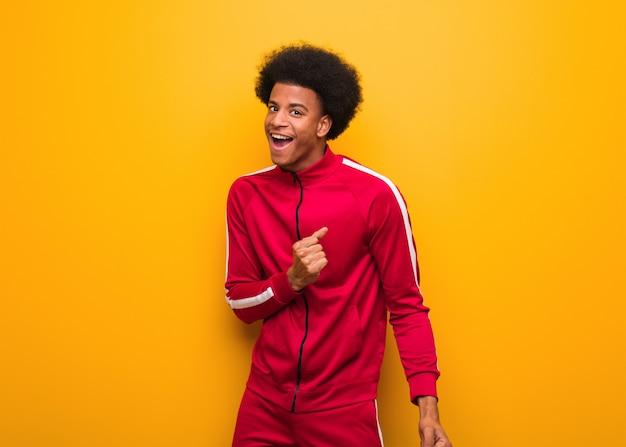 Homem jovem esporte preto sobre uma parede laranja dançando e se divertindo