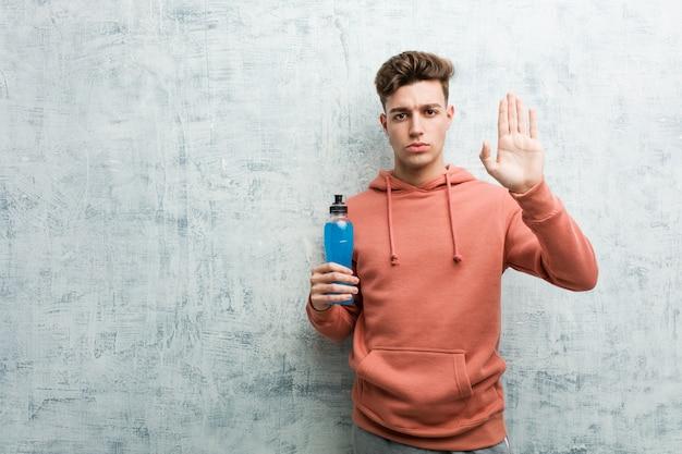Homem jovem esporte segurando uma bebida energética em pé com a mão estendida, mostrando o sinal de stop, impedindo-o.
