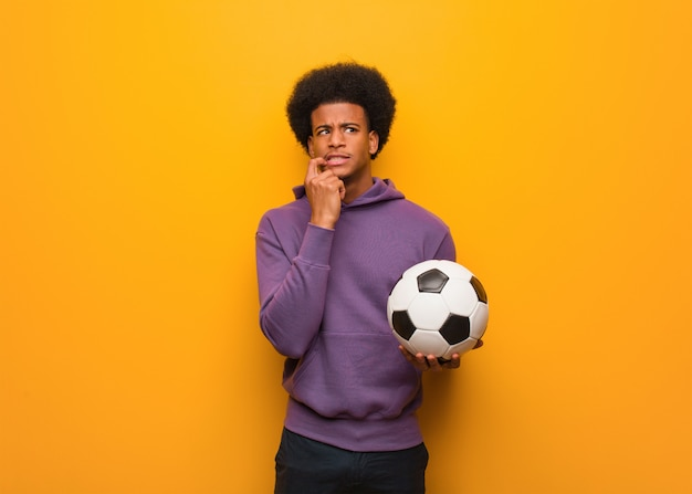 Homem jovem esporte segurando uma bola de futebol relaxado pensando em algo