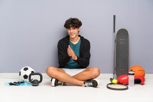 Homem jovem esporte sentado no chão em torno de muitos elementos de esporte aplaudindo