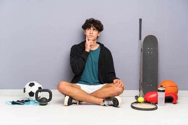 Homem jovem esporte sentado no chão em torno de muitos elementos de esporte pensando uma idéia