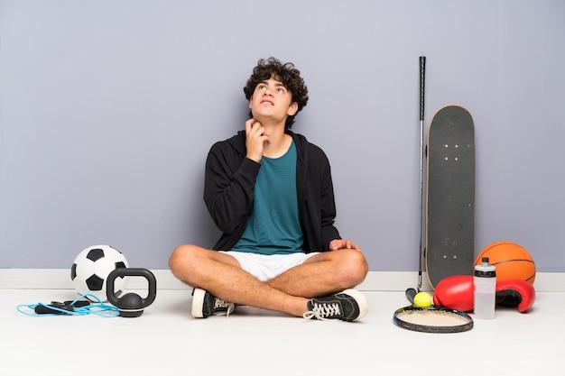 Homem jovem esporte sentado no chão em torno de muitos elementos de esporte, pensando uma idéia
