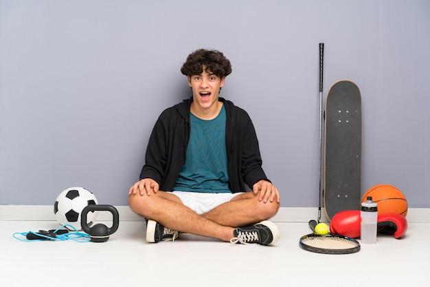 Homem jovem esporte sentado no chão em torno de muitos elementos do esporte com expressão facial de surpresa