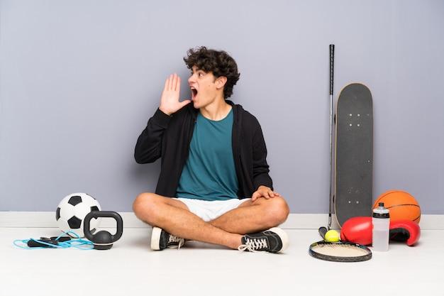 Homem jovem esporte sentado no chão em torno de muitos elementos do esporte gritando com a boca aberta