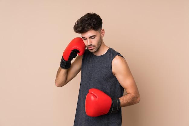 Homem jovem esporte sobre fundo isolado com luvas de boxe