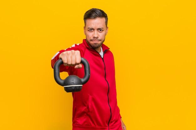 Homem jovem esporte sul-asiático segurando um haltere