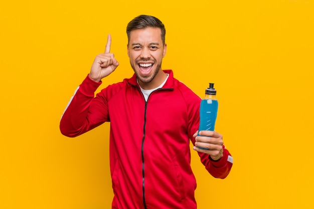 Homem jovem esporte sul-asiático segurando uma bebida energética.