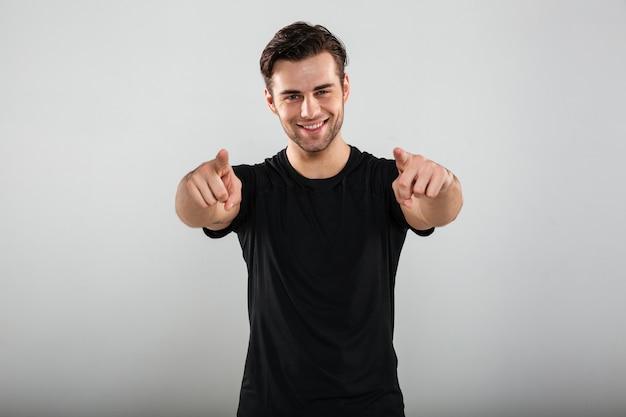 Homem jovem esportes apontando para você.
