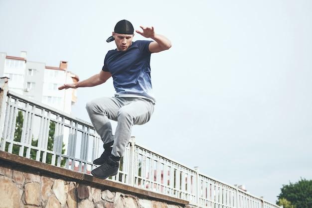 Homem jovem esportes fazendo parkour na cidade.