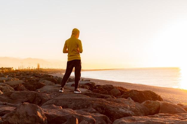 Homem jovem esportes no capô em pé sobre as rochas no fundo do mar e montanhas ao pôr do sol