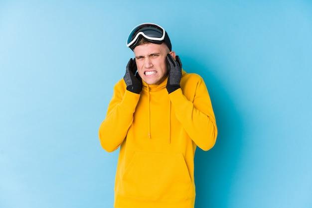 Homem jovem esquiador cobrindo os ouvidos com as mãos.
