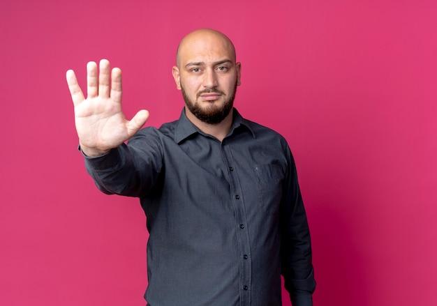 Homem jovem estrito careca de call center fazendo gesto de parada na frente, isolado na parede vermelha