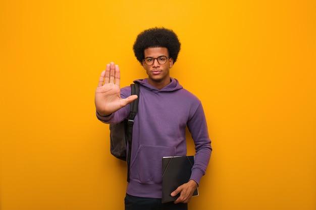 Homem jovem estudante afro-americano, colocando a mão na frente